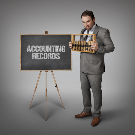 accounting records: Accounting records text on blackboard with businessman and abacus