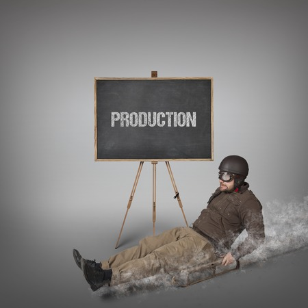 sledging people: Production text on blackboard with businessman sliding with a sledge Stock Photo