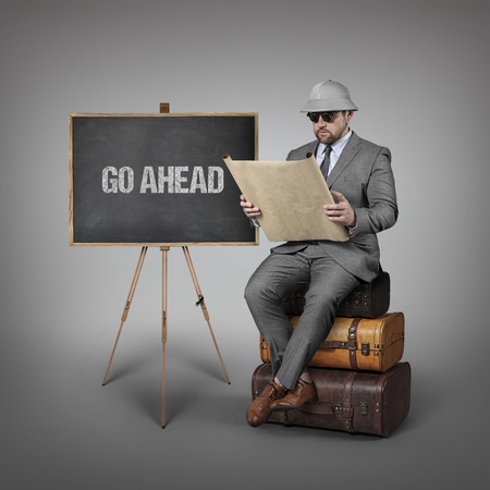 go ahead: Go Ahead text on  blackboard with explorer businessman sitting on suitcases