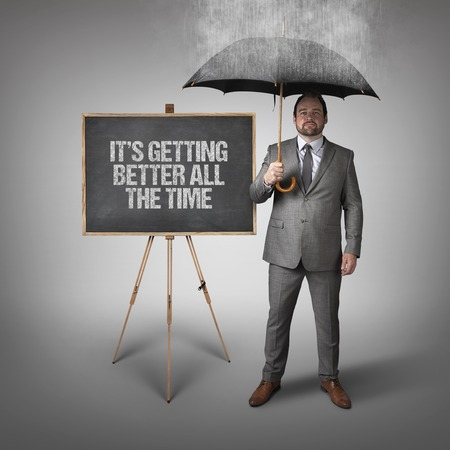 completely: Its getting better all the time text on blackboard with businessman and umbrella Stock Photo