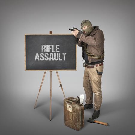 armaments: Rifle assault text on blackboard with terrorist holding machine gun