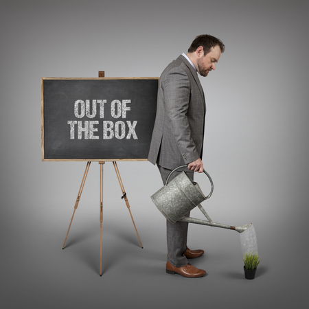 odd jobs: Out of the box text on  blackboard with businessman watering plant
