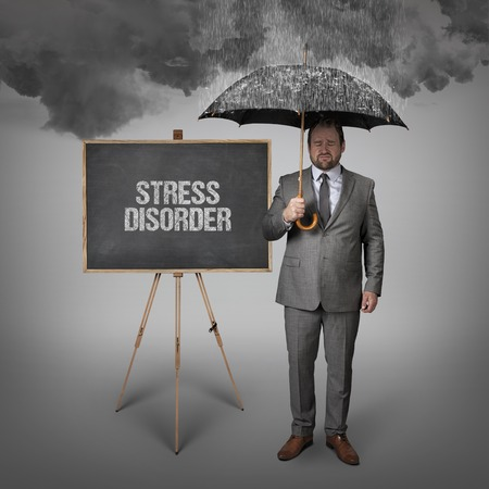 rehabilitated people: stress disorder text on blackboard with businessman holding umbrella