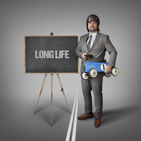 lifespan: Long life text on blackboard with businessman and toy car