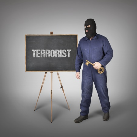 delincuencia: Terrorist text on blackboard with thief and key