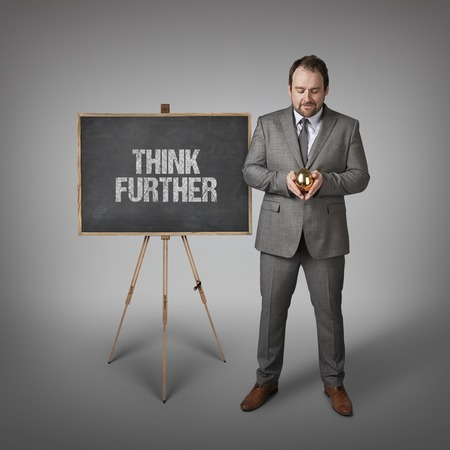 further: Think further text on  blackboard with businessman and golden egg Stock Photo