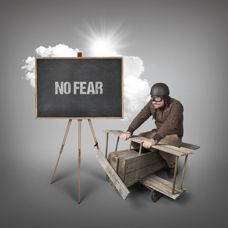 no fear: No fear text on blackboard with businessman and wooden aeroplane