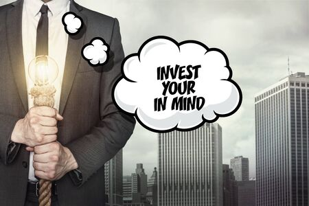 ability to speak: Invest your in mind text on speech bubble with businessman holding lamp