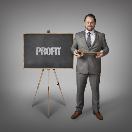 takings: Profit text on  blackboard with businessman and key Stock Photo