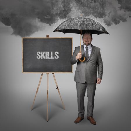 competences: skills text on blackboard with businessman holding umbrella