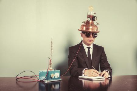 Businessman sitting at office desk with vintage goggles Standard-Bild