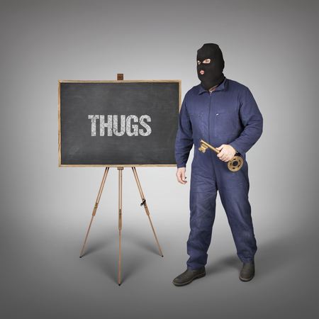 delincuencia: Thugs text on blackboard with thief and key Foto de archivo