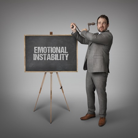 unevenness: Emotional instability text on blackboard with businessman drilling his head Stock Photo