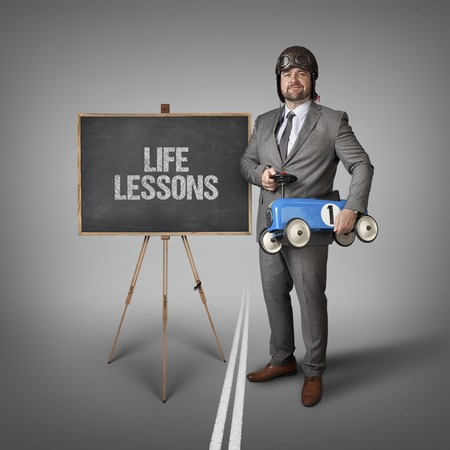 lifespan: Life lessons text on blackboard with businessman and toy car Stock Photo