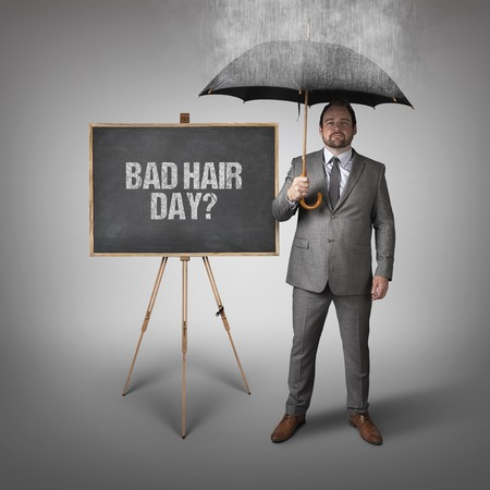 bad hair: Bad hair day text on blackboard with businessman and umbrella