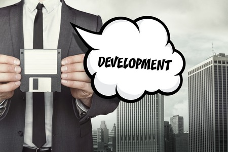 growth enhancement: Development text on speech bubble with businessman holding diskette