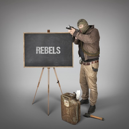 traitor: Rebels text on blackboard with terrorist holding machine gun