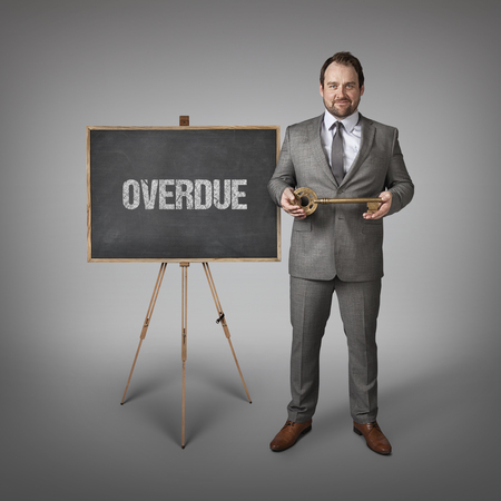 unsettled: Overdue text on  blackboard with businessman and key Stock Photo