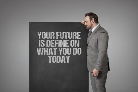 define: Your future is define on what you do today text on blackboard with businessman standing side Stock Photo