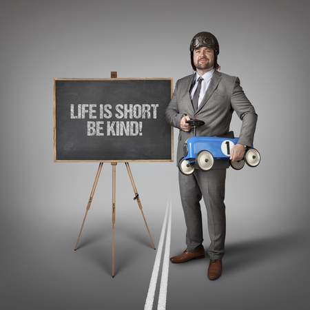 lifespan: Life is short be kind text on blackboard with businessman and toy car