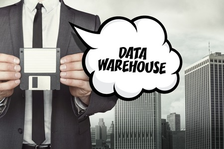 depository: Data warehouse text on speech bubble with businessman holding diskette Stock Photo