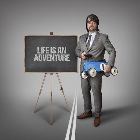 lifespan: Life is an adventure text on blackboard with businessman and toy car
