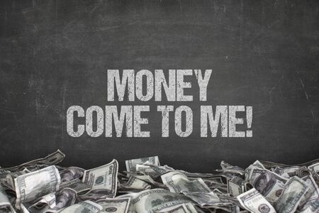 Money come to me  text on black background with dollar pile Stock Photo