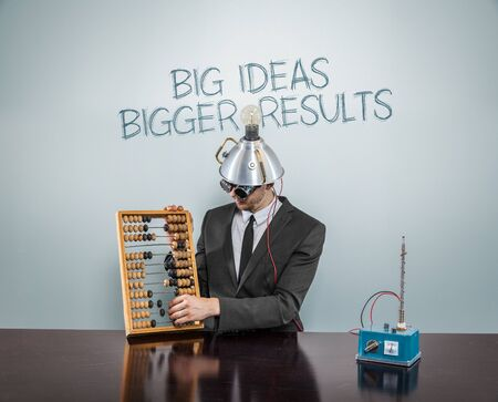consequence: Big  ideas  bigger text on blackboard with businessman and abacus Stock Photo