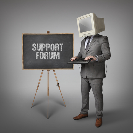 provision: Support forum text on blackboard and computer monitor on businessman head Stock Photo