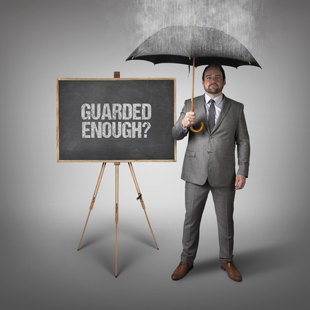 guarded: Guarded enough text on blackboard with businessman and umbrella