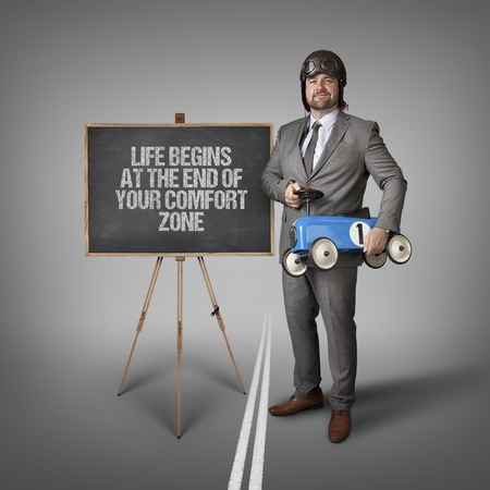 begins: Life begins at the end of your comfort zone text on blackboard with businessman and toy car