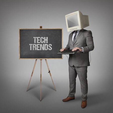 tendencies: Tech trends text on blackboard with businessman Stock Photo
