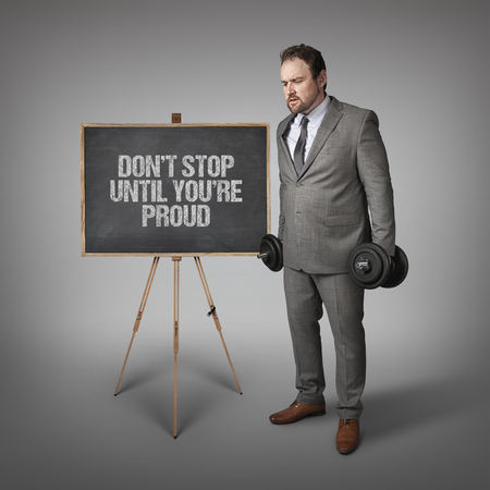 gratified: Don t stop until youre proud text on blackboard with businesssman