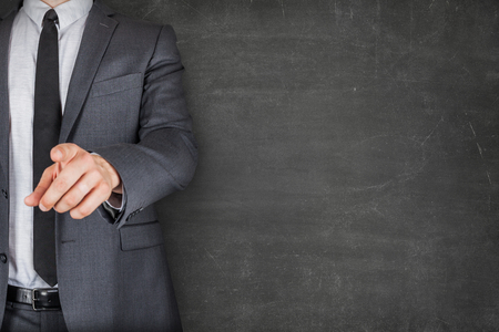 Businessman Pointing While Standing By Blackboard