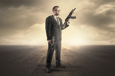 Businessman holding machine guns