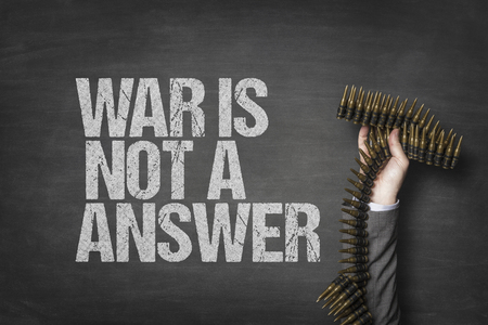 War is not a answer text on blackboard with businessman hand holding ammunition Stock Photo