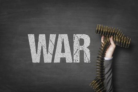 War text on blackboard with businessman hand holding ammunition Stock Photo