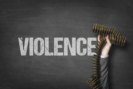 Violence text on blackboard with businessman hand holding ammunition