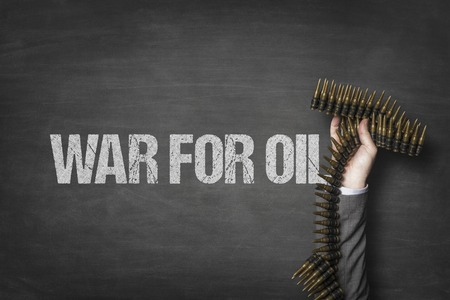 War for oil text on blackboard with businessman hand holding ammunition