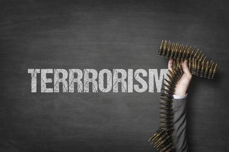 Terrorism text on blackboard with businessman hand holding ammunition