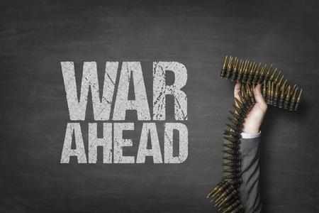 War ahead text on blackboard with businessman hand holding ammunition Stock Photo