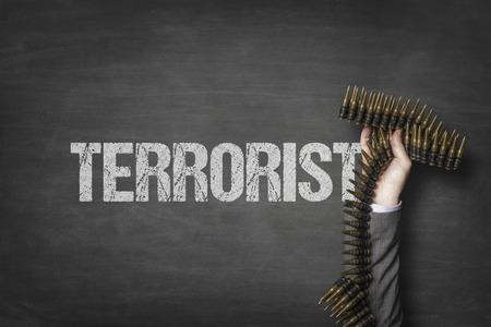 Terrorist text on blackboard with businessman hand holding ammunition