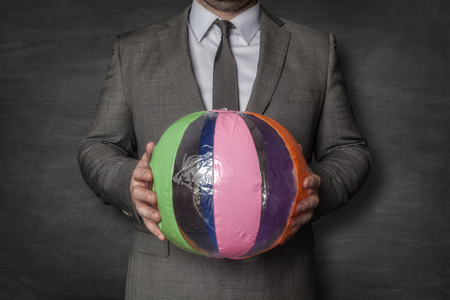 Businessman in a suit holding colourfull ball in hands Imagens