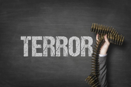 Terror text on blackboard with businessman hand holding ammunition