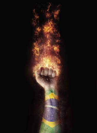 Brazil flag in a hand which is on a fire Imagens