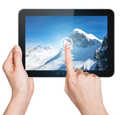 Tablet concept with pointing finger and snowy mountain picture in tablet screen Imagens