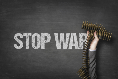 Stop war text on blackboard with businessman hand holding ammunition Stock Photo