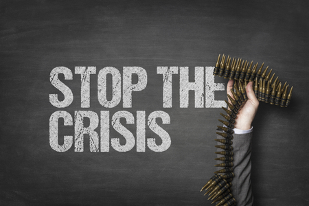 Stop the crisis text on black blackboard with businessman hand holding ammunition