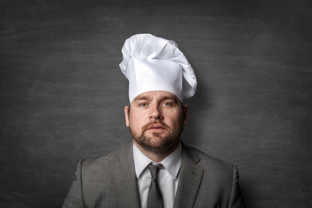 Businessman wearing a cook hat Imagens