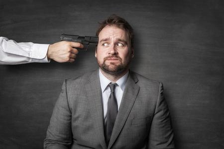 Evil boss holding a gun on businessman head Banco de Imagens